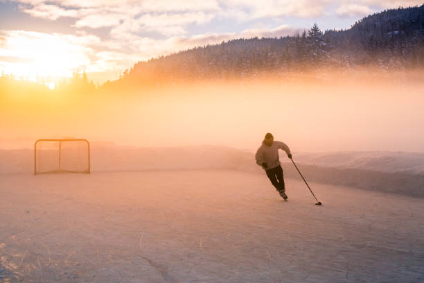 Young man playing hockey on frozen lake. stock photo
