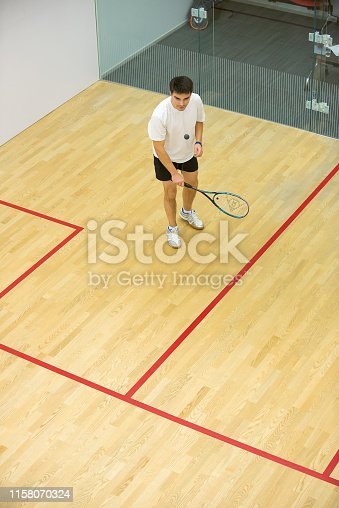 Squash player in action on squash court, front view/Young man playing match of squash