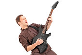 Young man playing on electric guitar, isolated on white background