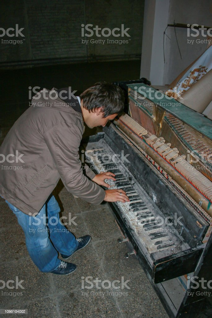 , Moscow, Russia. A young man playing piano. An old piano in dark...