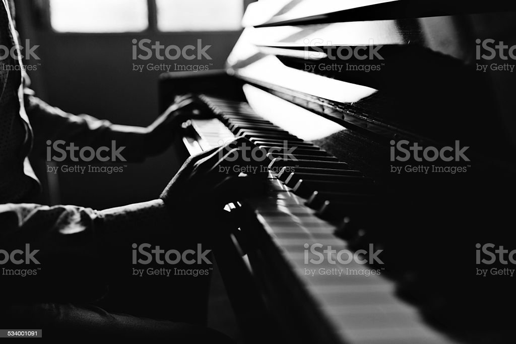 Young man playing piano Piano and human hand with black and white silhouette technic. 2015 Stock Photo