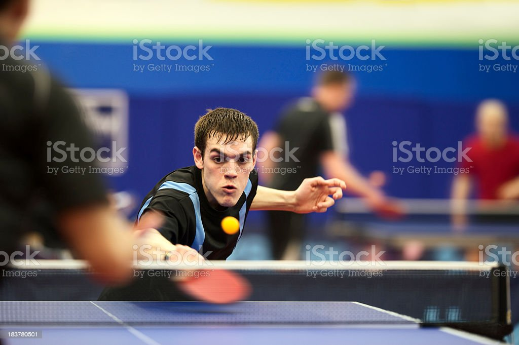 Young man playing ping pong with red racket stock photo