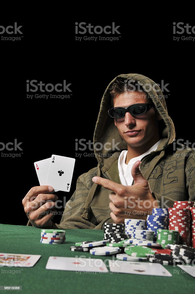 Young man playing poker and holding a couple of aces royalty-free stock photo