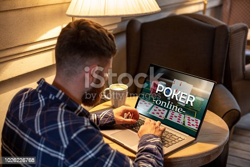 istock Young man playing poker via netbook during work-break in coffee shop, male sitting in front open laptop computer 1026226768