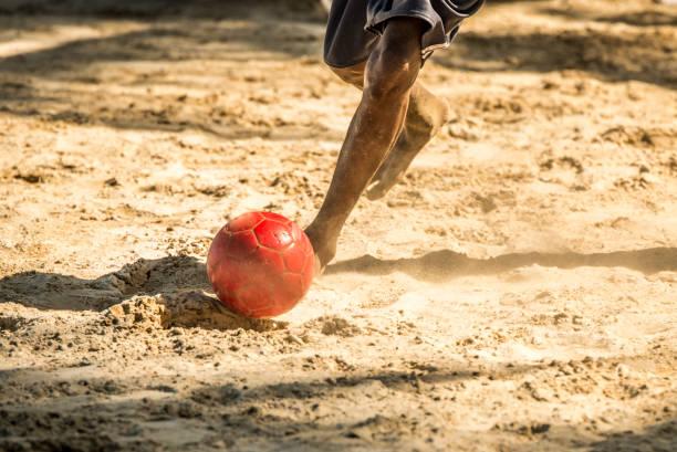 homem novo que joga o futebol da areia - futebol de areia - fotografias e filmes do acervo