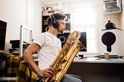 Young man playing saxophone recording in studio