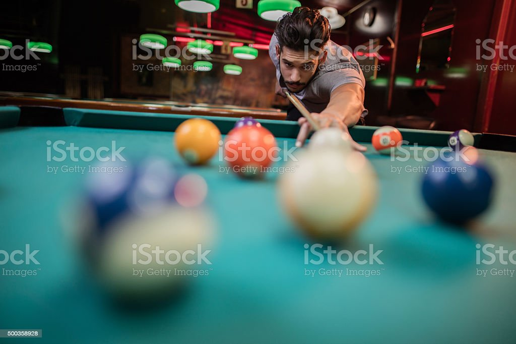 Young man playing snooker in a pub. stock photo
