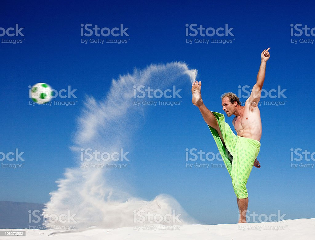 Young Man Playing Soccer on Beach royalty-free stock photo