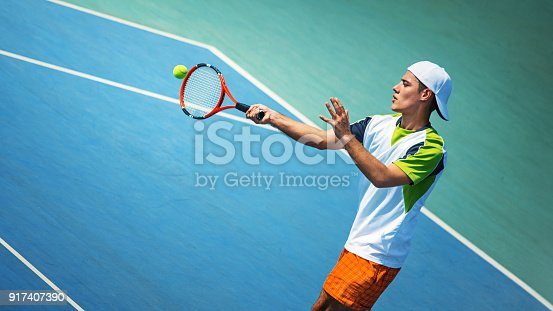 1153628111istockphoto Young man playing tennis. 917407390