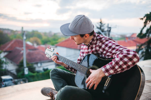 young man playing the guitar at terrace - musicians singers during lockdown foto e immagini stock