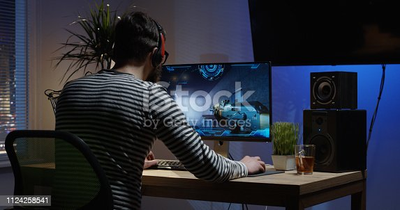 Medium shot of a young man playing shooting video game inside a room