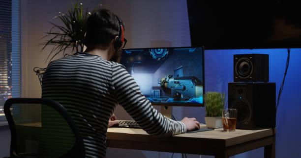 jonge man spelen video game in een kamer - gaming stockfoto's en -beelden