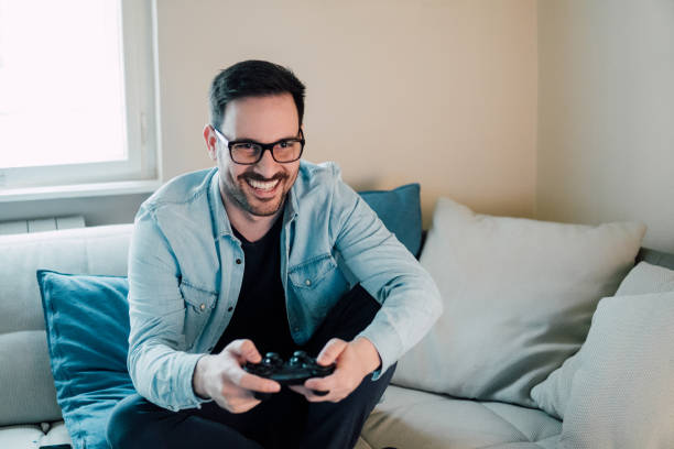 young man playing video games - man joystick imagens e fotografias de stock