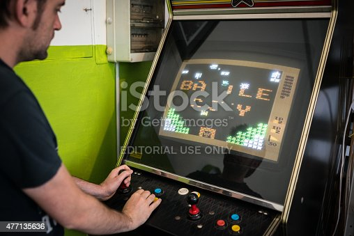istock Young man playing vintage arcade videogame 477135636
