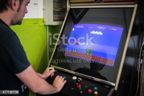 istock Young man playing vintage arcade videogame 477135726