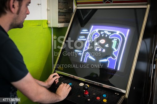 istock Young man playing vintage arcade videogame 477136784