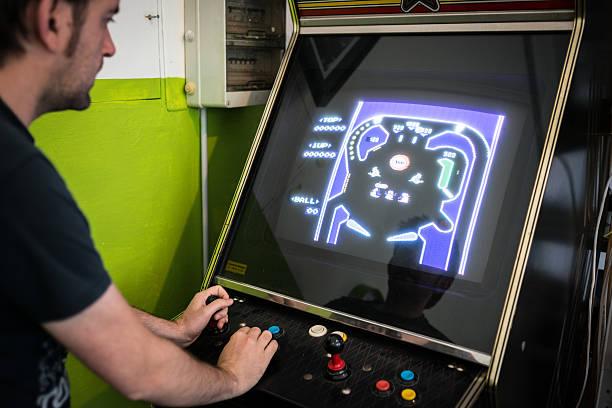 junger mann spielen videospiel-arcade - pinball spielen stock-fotos und bilder