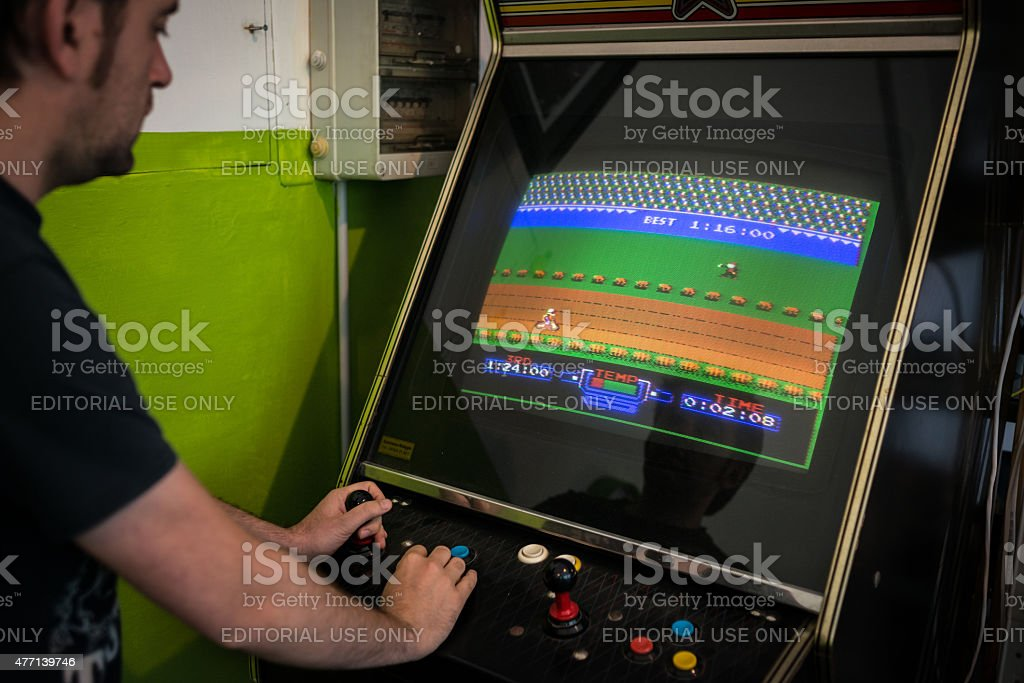 Young man playing vintage arcade videogame stock photo