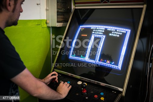 istock Young man playing vintage arcade videogame 477139848