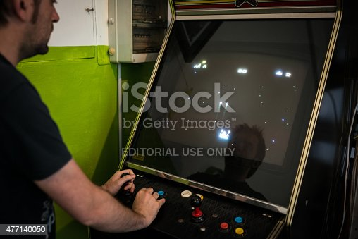 istock Young man playing vintage arcade videogame 477140050