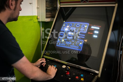istock Young man playing vintage arcade videogame 477140460