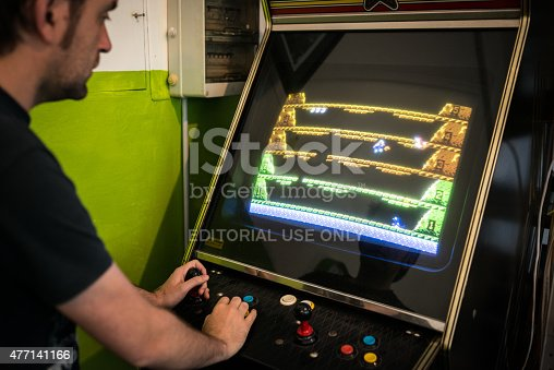 istock Young man playing vintage arcade videogame 477141166