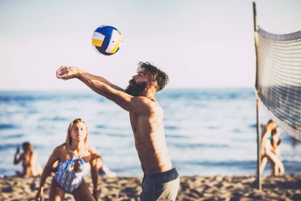 Young man playing volleyball with friends on the beach. stock photo