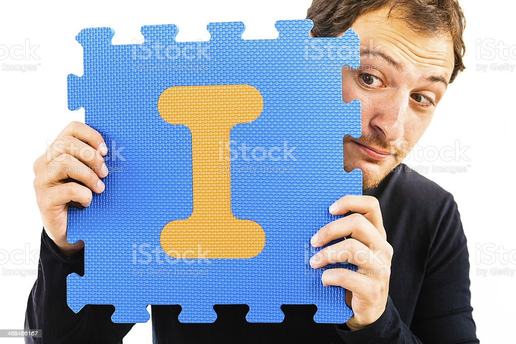 Young Man Playing with Alphabet Puzzle, Letter I royalty-free stock photo