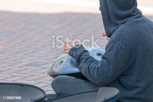 Varna, Bulgaria - May 16 2019: Young man playing with an Hang (also known as handpan).