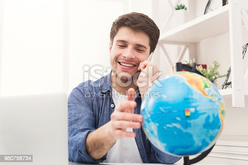 istock Young man playing with globe and taking on phone 950758734