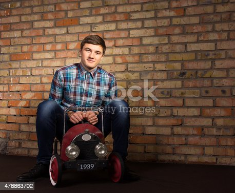 496487362istockphoto Young Man Playing with Toy Automobile 478863702