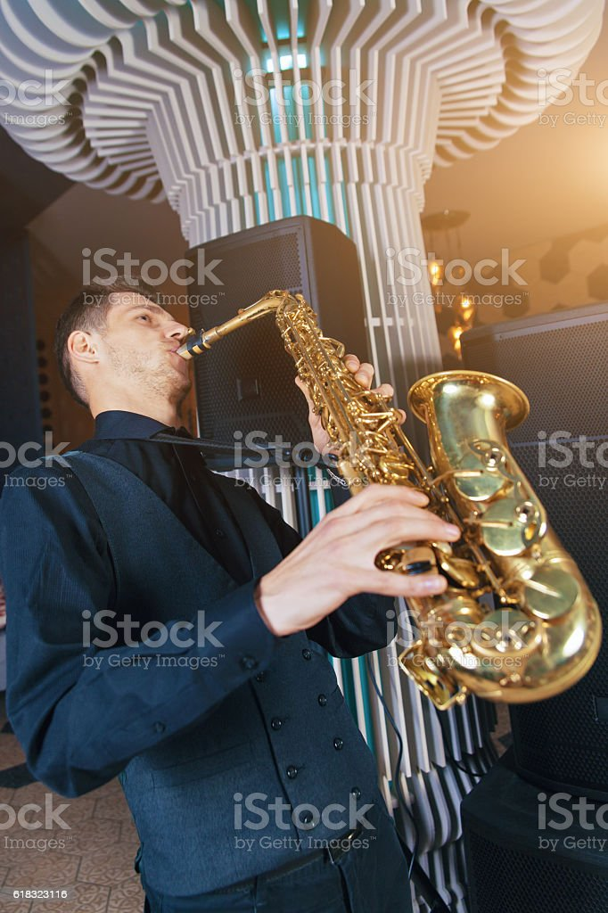 Young man plays a musical instrument saxophone stock photo