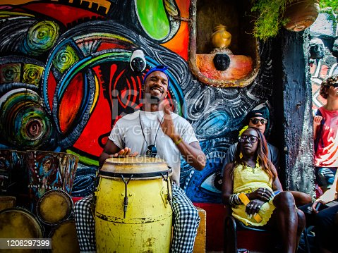 Havana - April 29, 2018: An unknown young man plays the conga drum during a Sunday presentation in the picturesque Hammel Alley placed in Centro Habana, Cuba, on April 29, 2018.