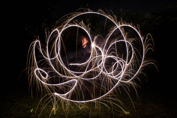 A young man plays with a sparkler at night stock photo