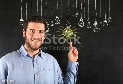 539247613istockphoto Young Man Pointing a Light bulb Sketched on Blackboard 537818877