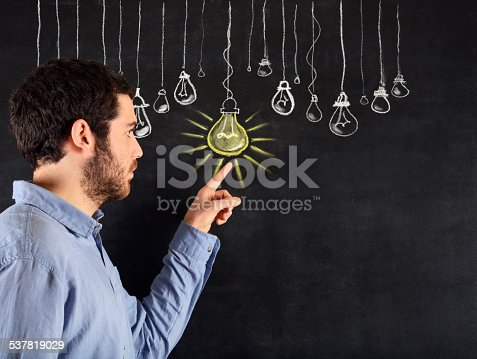539247613istockphoto Young Man Pointing a Light Bulb Sketched on Blackboard 537819029
