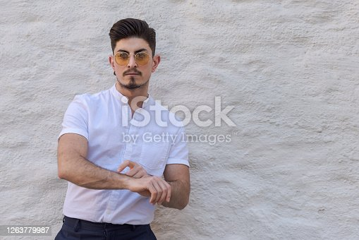 Young man pointing at imaginary wristwatch on his forearm as