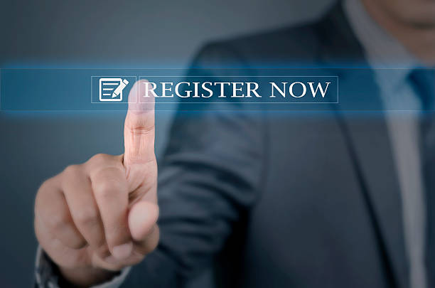 Young man pointing into register now stock photo