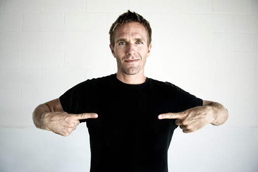 Young man with blank expression pointing to the copy space in his black t-shirt; bleach bypassed to enhance grittiness