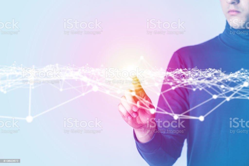 jeune homme pointant vers l'interface futuriste - Photo
