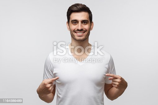 1018069806 istock photo Young man pointing to his white t-shirt with fingers, showing empty space for your advertising, standing isolated on gray background 1164586489