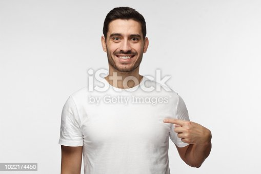 1018069806 istock photo Young man pointing with index finger at blank white t-shirt with empty space for your advertising text or image, standing isolated on gray background 1022174450