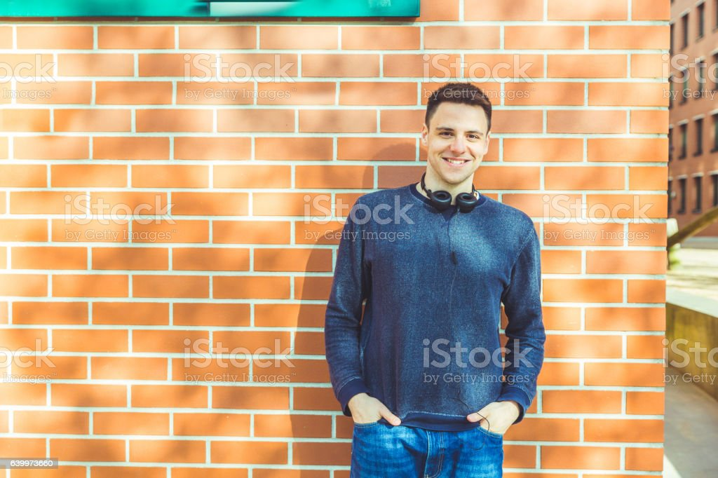 Young man portrait against a brick wall stock photo