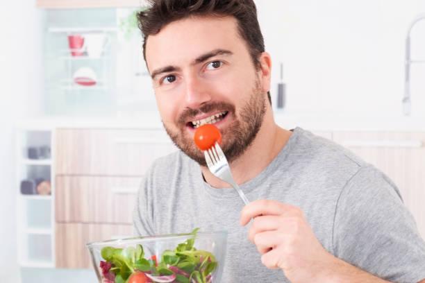 junger mann porträt zu diät und ernährung frischen salat - abnehmen leicht gemacht stock-fotos und bilder