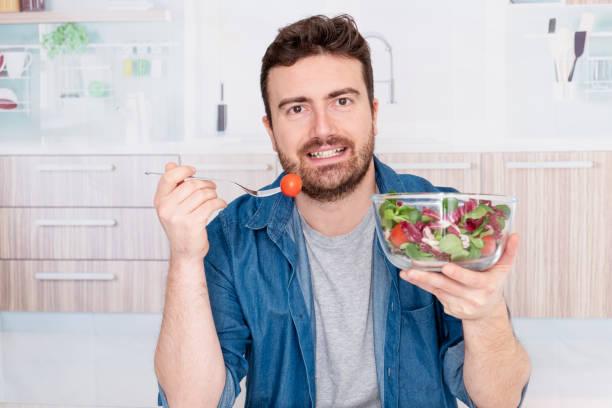 junge mann porträtiert diät und isst frischen salat - abnehmen leicht gemacht stock-fotos und bilder