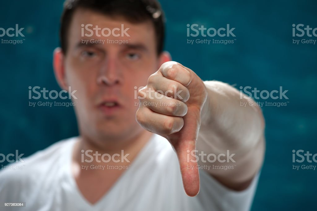 Young man posing on blue background Dislike. Close-up portrait of positive man in white shirt showing thumbs down gesture on blue background. Adult Stock Photo