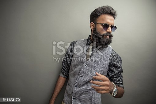 Young man posing with beard in suit with eye wear on grey background