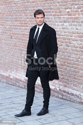 full length picture of an elegant young business man posing on a sidewalk next to a brick wall, with his hands in his pockets and looking into the camera