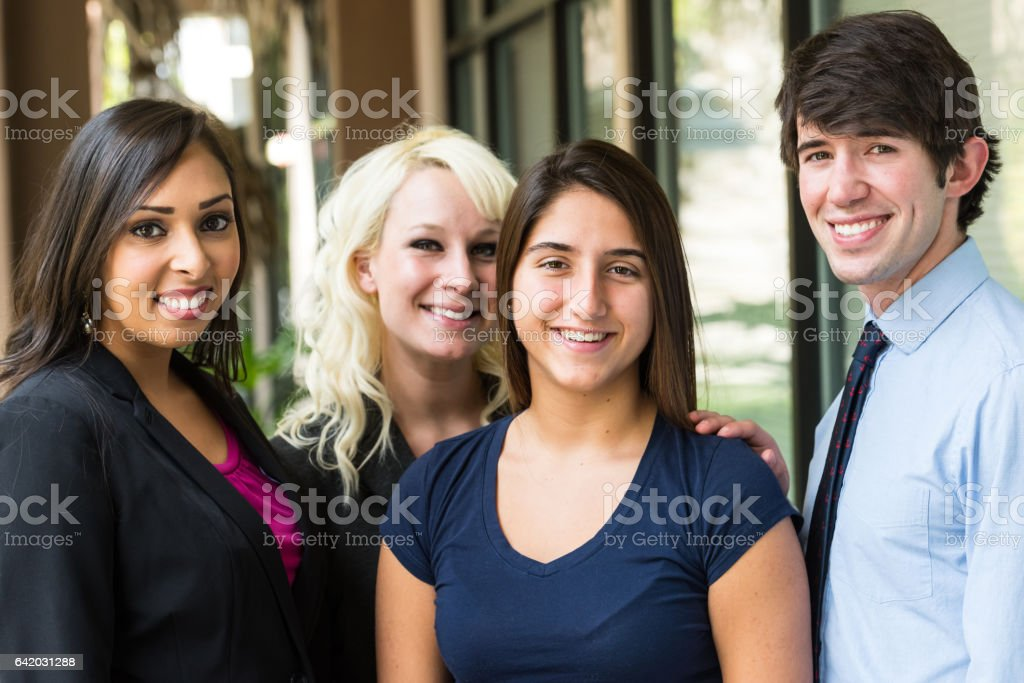 Young man posing with three young women stock photo