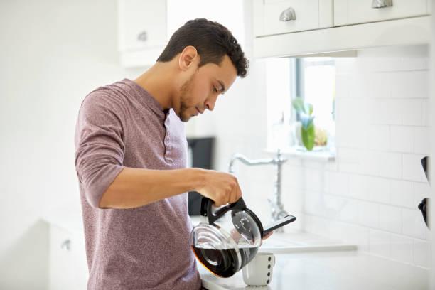 Junger Mann gießt Kaffee in der Tasse zu Hause – Foto